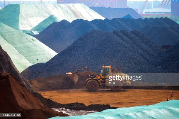 TOPSHOT This photo taken on May 15 2019 shows an excavator transferring imported iron ore at a port in Rizhao in China's eastern Shandong province /...