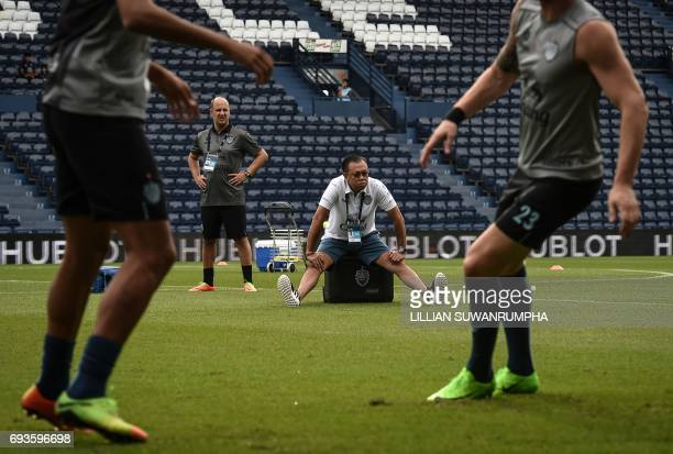 This photo taken on May 17, 2017 shows 58-year-old former Thai MP, Newin Chidchob , watching Buriram United football players warm up before a Thai...