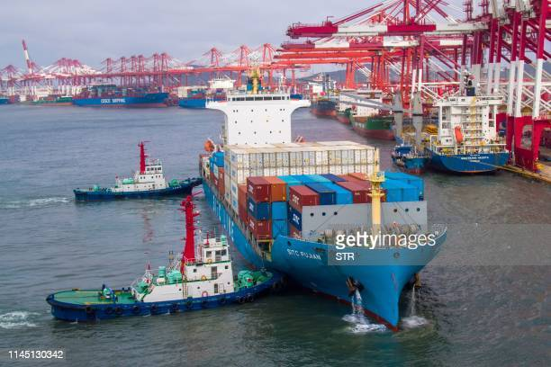This photo taken on May 17 2019 shows a container ship berthing at the port in Qingdao in China's eastern Shandong province EU firms are caught in...