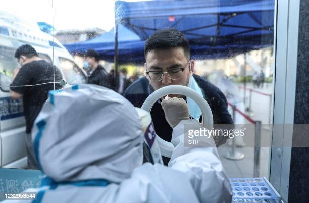 This photo taken on May 17, 2021 shows a man receiving a Covid-19 nucleic acid test at a hospital in Shenyang in China's northeastern Liaoning...