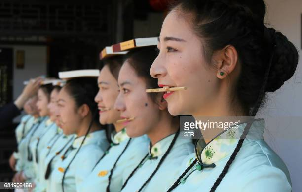 This photo taken on May 18 2017 shows tour guides from Slender West Lake scenic attending an etiquette training for China Tourism Day on May 19 / AFP...