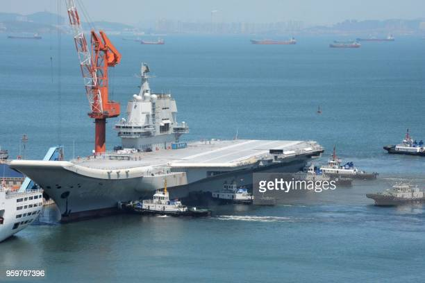 This photo taken on May 18 2018 shows tugs guiding China's first domestically manufactured aircraft carrier known as Type 001A as it returns to port...