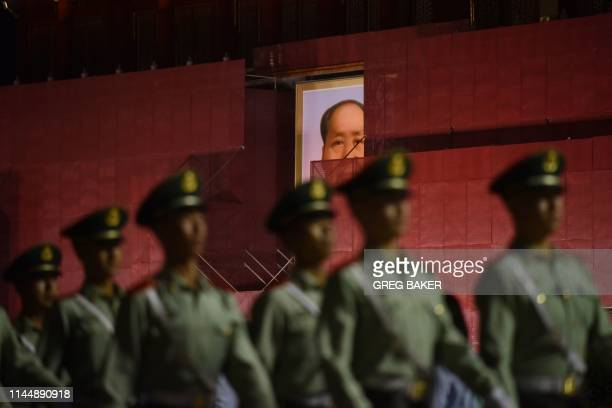TOPSHOT This photo taken on May 18 2019 shows paramilitary police officers marching past the portrait of late communist leader Mao Zedong on...