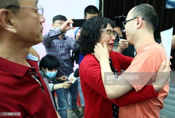 This photo taken on May 18 2020 shows Mao Yin reuniting with his mother Li Jingzhi and father Mao Zhenping in Xian in China's northern Shaanxi...