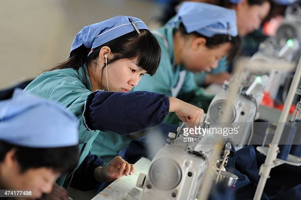 This photo taken on May 19, 2015 shows workers producing clothes in a factory in Huaibei, east China's Anhui province. China's manufacturing activity...