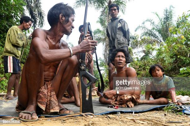 This photo taken on May 19 2017 shows Indonesian Orang Rimba tribesmen brandishing homemade rifles and wearing loincloths preparing to set out...