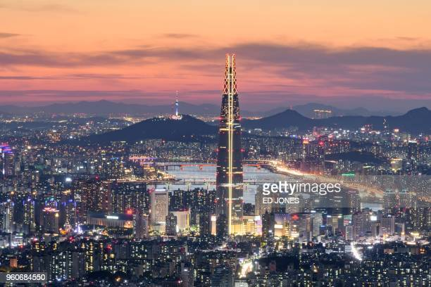 TOPSHOT This photo taken on May 19 2018 shows a general view of the Lotte tower and Namsan tower amid the Seoul city skyline and Han river during...