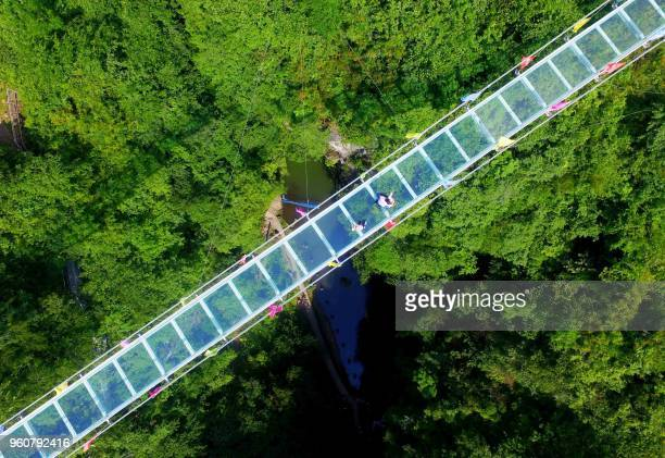 This photo taken on May 19, 2018 shows an aerial view of people walking on a glass-bottomed skywalk at Shimenxian Lake in Rongan in south China's...