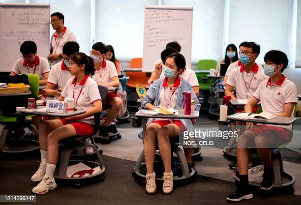 This photo taken on May 19 2020 shows newlyhired Huawei employees attending a class at Huawei University in Dongguan in China's southern Guangdong...