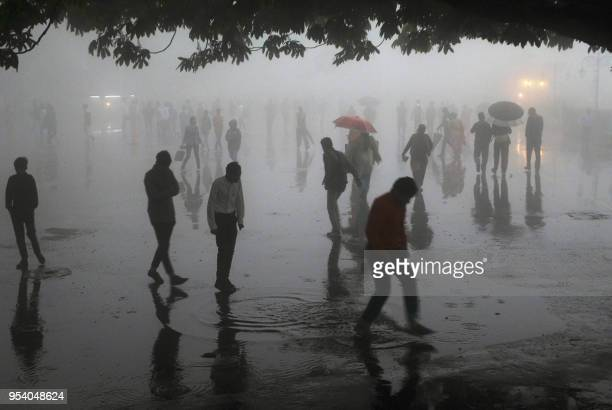 TOPSHOT This photo taken on May 2 2018 shows people walking under heavy rainfall in the northern hill town of Shimla in Himachal Pradesh state Dust...