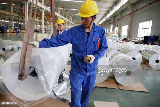 This photo taken on May 20 2017 shows Chinese workers loading aluminium tapes at an aluminium production plant in Huaibei east China's Anhui province...