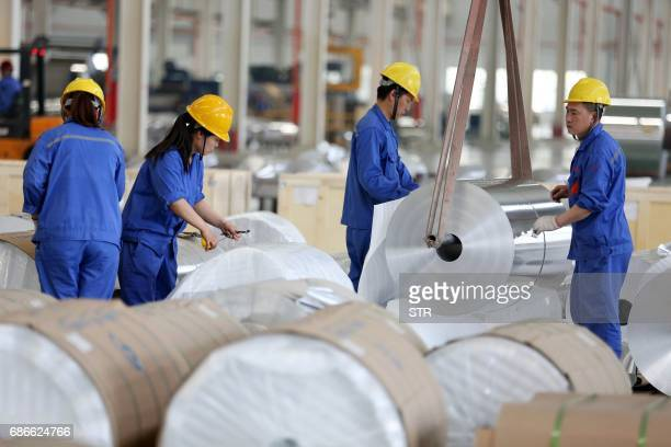 This photo taken on May 20 2017 shows Chinese workers packaging aluminium tapes at an aluminium production plant in Huaibei east China's Anhui...