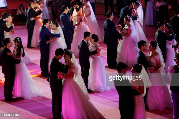 TOPSHOT This photo taken on May 20 2018 shows couples kissing each other during a mass wedding ceremony at Northeastern University in Shenyang in...