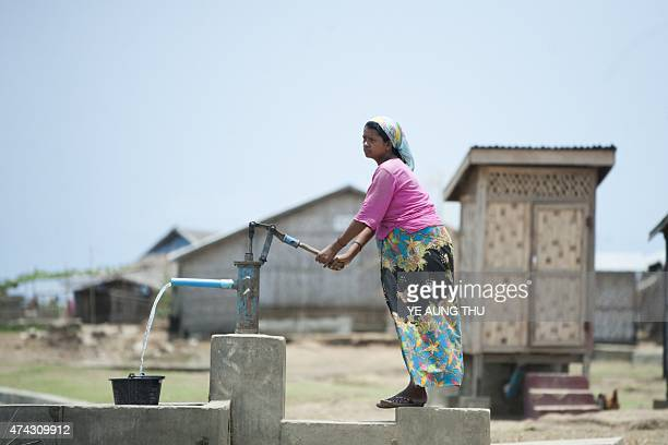 This photo taken on May 21 2015 shows an ethnic Rohingya Muslim pregnant woman collecting water from a well at a camp set up outside the city of...