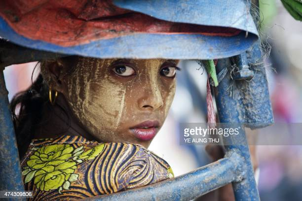 This photo taken on May 21 2015 shows an ethnic Rohingya Muslim woman looking back as she rides a tuk tuk near a camp set up outside the city of...