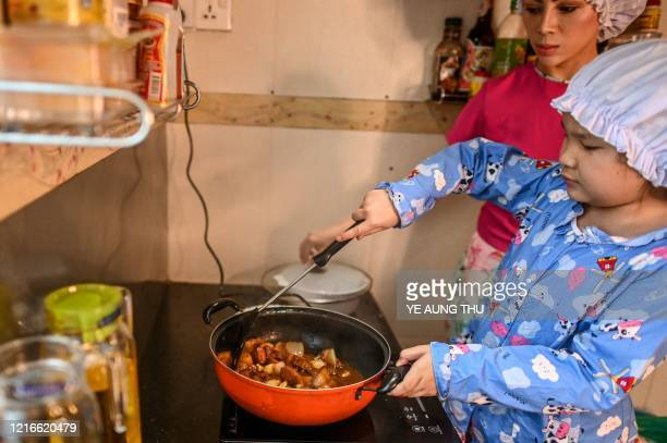 This photo taken on May 21, 2020 shows Moe Myint May Thu and her mother Honey Cho cooking while filming a video at their house in Yangon. - From...