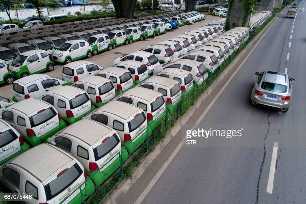 This photo taken on May 22 2017 shows a car passing new electric vehicles parked in a parking lot under a viaduct in Wuhan central China's Hubei...