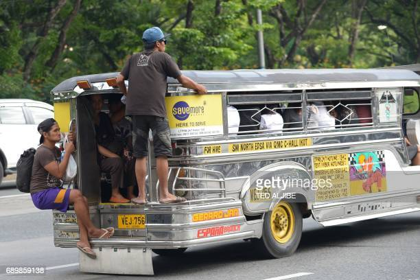 This photo taken on May 22 2017 shows communters holding on while riding a jeepney in Manila Jeepneys once hailed as the 'King of the Road' and a...