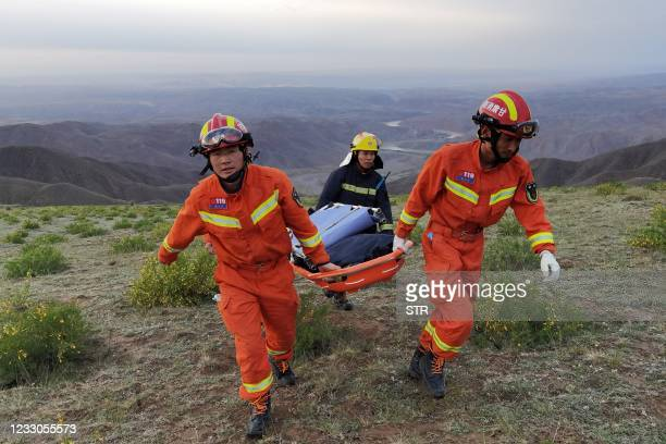 This photo taken on May 22, 2021 shows rescuers carrying equipment as they search for runners who were competing in a 100-kilometre cross-country...