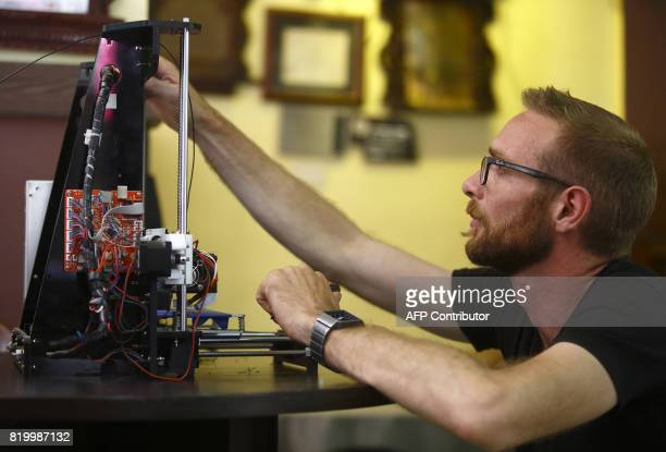 This photo taken on May 23 2017 shows Disaster Hack founder Matthew Rockwell setting up a 3D printer in Kathmandu Disaster Hack is a nonprofit...