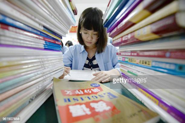 """This photo taken on May 23, 2018 shows a high school student going through exam papers, ahead of the annual """"Gaokao"""" or college entrance examinations..."""