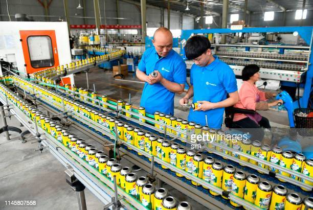 This photo taken on May 23 2019 shows workers checking aerosol in a factory which produces for export to Brazil Argentina Chile Egypt India and other...