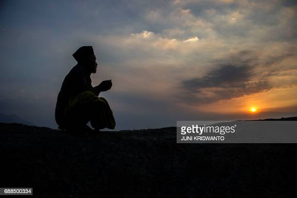 This photo taken on May 25 2017 shows an Indonesian man offering prayers to victims of the Lapindo mud volcano tragedy to mark the 11th anniversary...