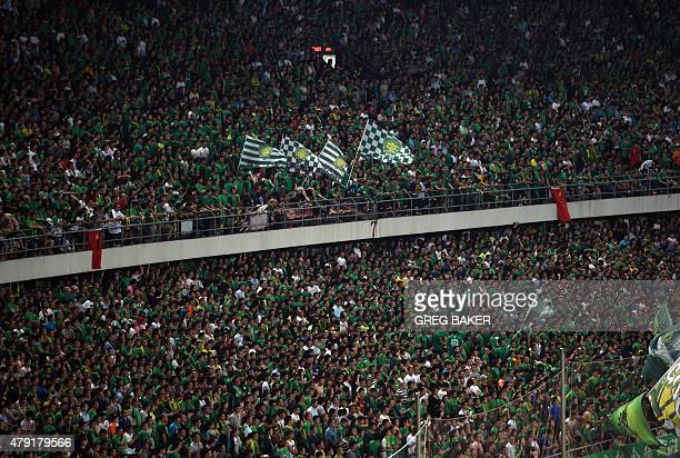 This photo taken on May 26 2015 shows fans of the Beijing Guoan football team cheering in support during their match against Jeonbuk Hyundai Motors...