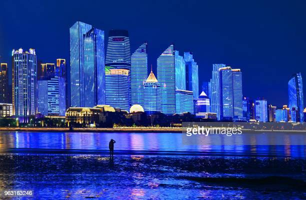 TOPSHOT This photo taken on May 26 2018 shows a visitor looking at illuminated buildings in Qingdao in China's eastern Shandong province This year's...