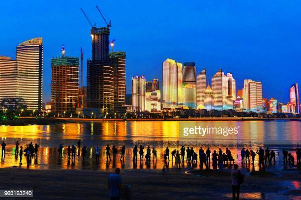 TOPSHOT This photo taken on May 26 2018 shows residents and visitors looking at illuminated buildings in Qingdao in China's eastern Shandong province...