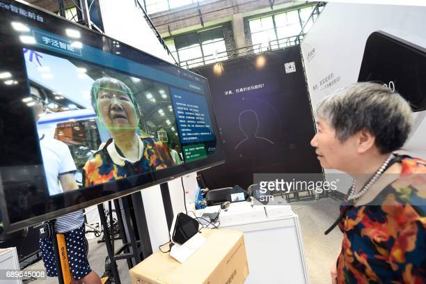This photo taken on May 27 2017 shows a woman looking at a screen displaying facial recognition technology at the Hangzhou International Future Life...