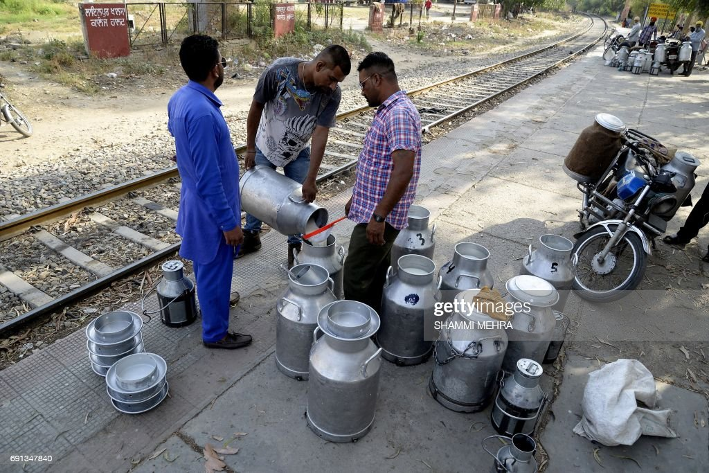 This photo taken on May 27 2017 shows Indian milkmen transferring milk between containers on the platform of a railway station as they work to supply.