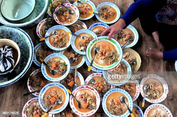 This photo taken on May 27 2018 shows a woman serving porridge as people break fast during Ramadan at a mosque in Bantul Yogyakarta Muslims...