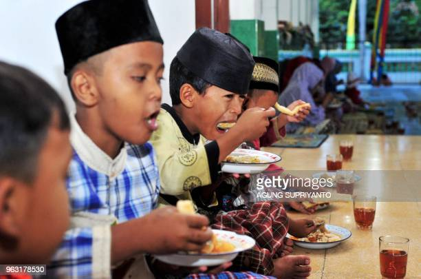 This photo taken on May 27 2018 shows boys eating porridge as they break fast during Ramadan at a mosque in Bantul Yogyakarta Muslims throughout the...