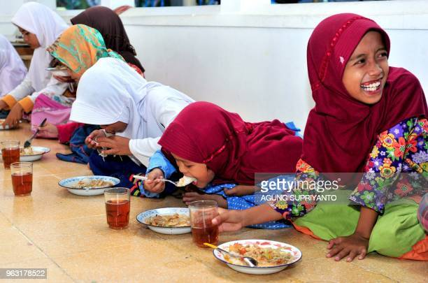 This photo taken on May 27 2018 shows girls eating porridge as they break fast during Ramadan at a mosque in Bantul Yogyakarta Muslims throughout the...