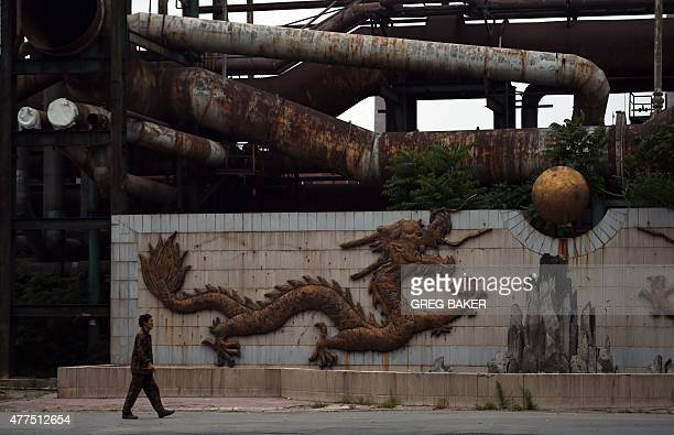This photo taken on May 28 2015 shows a worker walking past a sculpture of a dragon near rusting pipes at the Shougang Capital Iron and Steel plant...