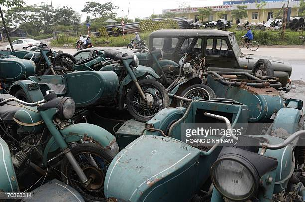 This photo taken on May 3 2013 shows motorcyclists riding past old Russianmade Sovietera bikes and sidecars displayed for sale at a private garage in...