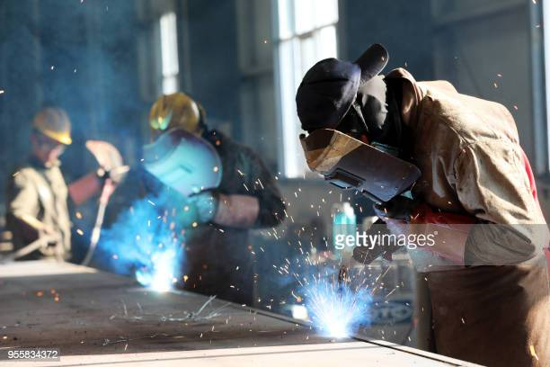 This photo taken on May 3, 2018 shows a worker cutting steel at a factory in Huaibei in China's eastern Anhui province. - China's surplus with the...