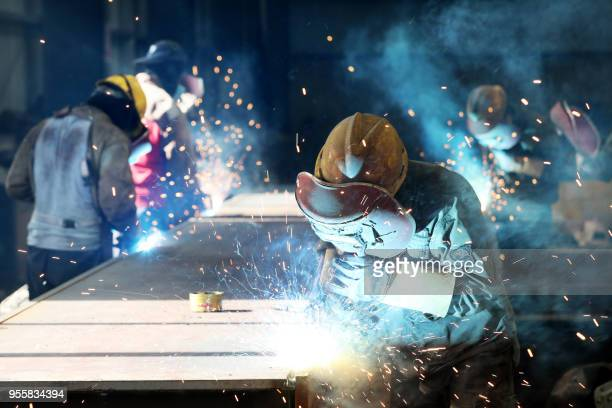This photo taken on May 3 2018 shows a worker cutting steel at a factory in Huaibei in China's eastern Anhui province China's surplus with the United...
