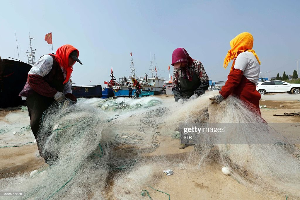 This photo taken on May 30, 2016 shows fisherfolk clearing up fishing gear at a port in Lianyuangang, eastern China's Jiangsu province. The three-month summer fishing moratorium will start on June 1. / AFP / STR / China OUT