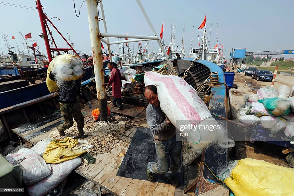 This photo taken on May 30, 2016 shows fishermen unloading fishing gear at a port in Lianyuangang, eastern China's Jiangsu province. The three-month summer fishing moratorium will start on June 1. / AFP / STR / China OUT