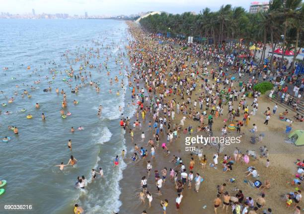 This photo taken on May 30 2017 shows crowds on a beach in Haikou on China's southern Hainan island Tens of thousands crowded beaches on the island...