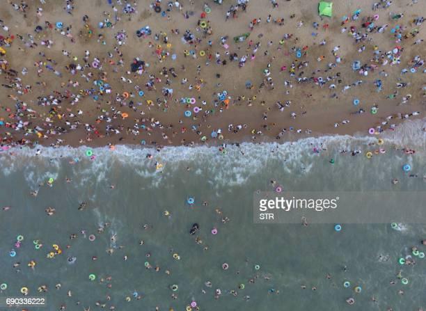 TOPSHOT This photo taken on May 30 2017 shows crowds on a beach in Haikou on China's southern Hainan island Tens of thousands crowded beaches on the...
