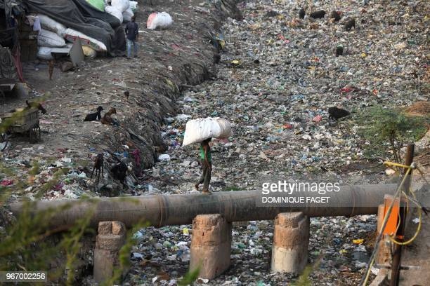 This photo taken on May 30 2018 shows a man carrying a bag containing plastic recyclable items as he walks on a water pipe next to a sewage drain...