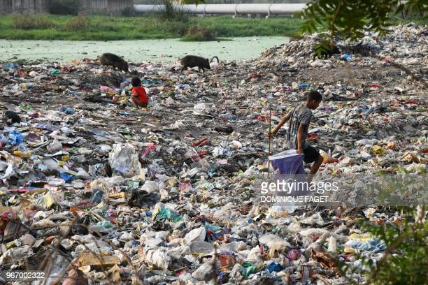This photo taken on May 30 2018 shows a rag picker walking along a sewage drain canal full of garbage in the Taimur Nagar slum area in New Delhi A...