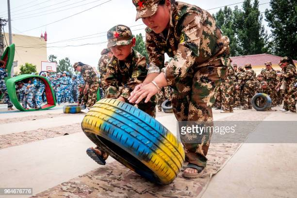 This photo taken on May 30 2018 shows children simulating a military drill at a kindergarten ahead of International Children's Day in Huaxian in...