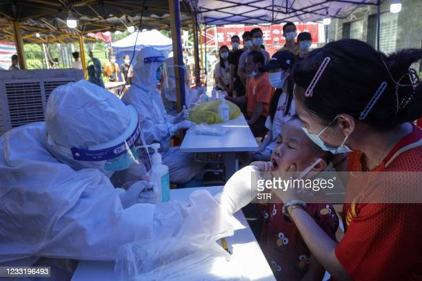 This photo taken on May 30, 2021 shows a child receiving a nucleic acid test for the Covid-19 coronavirus in Guangzhou in China's southern Guangdong...