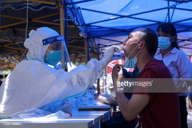 This photo taken on May 30, 2021 shows a man receiving a nucleic acid test for the Covid-19 coronavirus in Guangzhou in China's southern Guangdong...