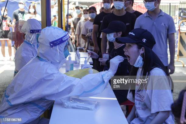 This photo taken on May 30, 2021 shows a woman receiving a nucleic acid test for the Covid-19 coronavirus in Guangzhou in China's southern Guangdong...