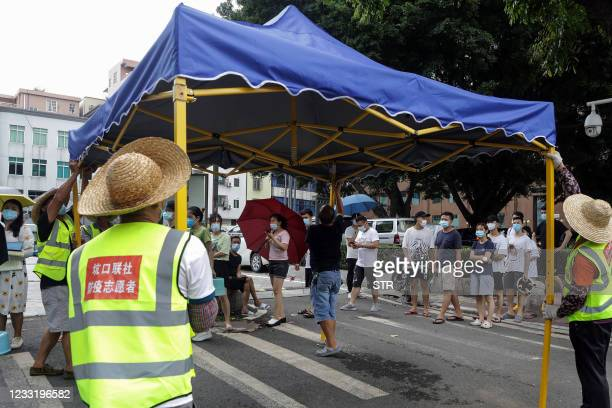 This photo taken on May 30, 2021 shows volunteers setting up a tent as residents prepare to receive nucleic acid tests for the Covid-19 coronavirus...
